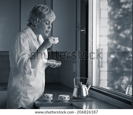 Serene morning moment, mature woman drinking coffee in the kitchen, sunlight coming from the window