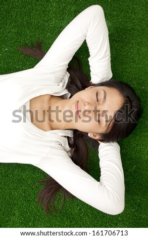 Serene young woman relaxing outdoor in fresh grass