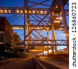 Series of gantry cranes in a harbor terminal at dusk - stock photo
