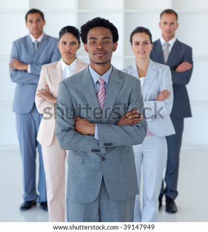 Serious Afro-American businessman standing in front of his team
