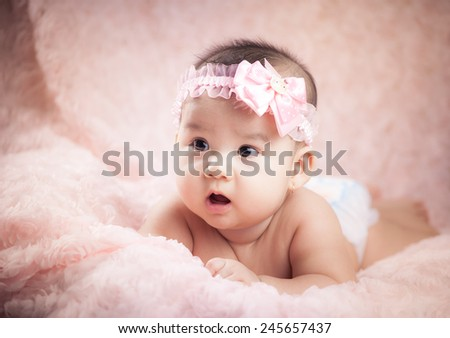 Serious baby girl looking at camera lying on pink background. Portrait of a little beautiful baby