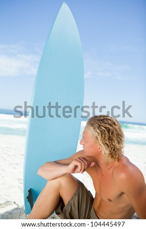 Serious blonde man sitting in front of the sea next to his blue surfboard