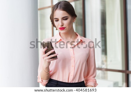 Serious business girl is sending message by phone