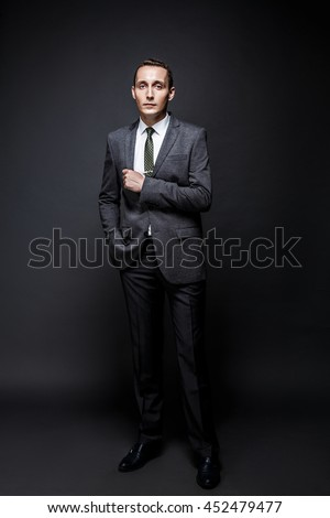 Serious business man brown hair with expressive face wearing grey suit and tie. Isolated on dark background.