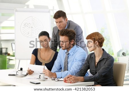 Serious business team reading papers at office meeting. Caucasian young businessman and businesswoman, suit, sitting at table, whiteboard in background.