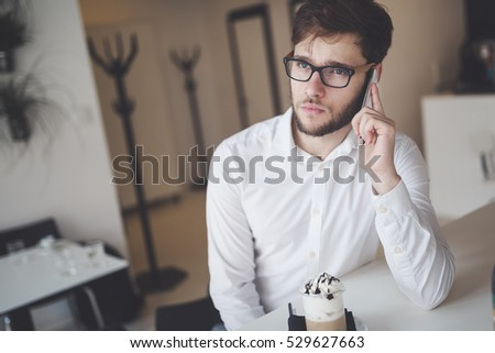 Serious businessman on coffee break using phone