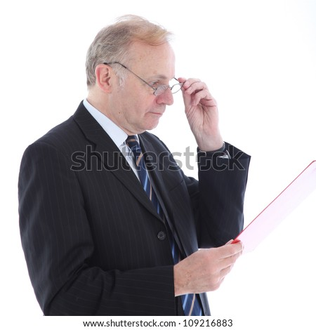 Serious businessman reading report Serious middle-aged businessman wearing glasses reading a report he is handholding isolated on white