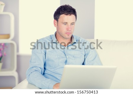 Serious casual man sitting on couch using laptop in bright living room