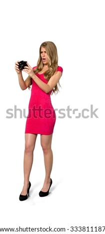 Serious Caucasian young woman with long light blond hair in evening outfit using camera - Isolated