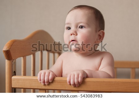 Serious chubby young baby with a focused look standing shirtless in a wooden cot gripping the rail with its hands and looking to the side with a thoughtful expression