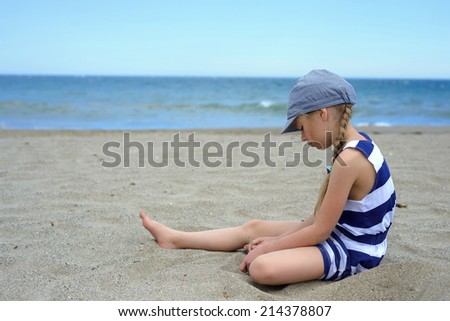 Serious cute little girl sitting on the beach