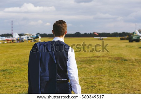 Serious handsome young man in the west and suit walk near small plane on the airfield.