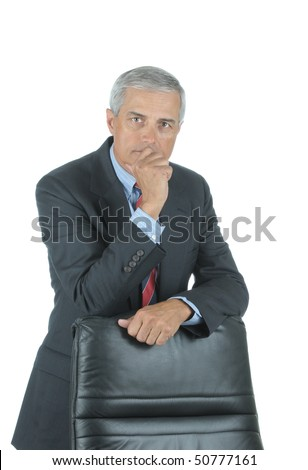 Serious Middle Aged Businessman leaning on chair back with hand on his chin isolated on white