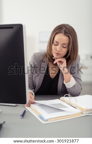 Serious Pretty Young Office Woman Reading Documents on her Desk with One Hand on her Chin