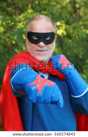 Serious senior super hero with black mask having crossed arms