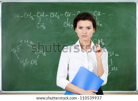 Serious teacher stands at the blackboard while holding blue notebook