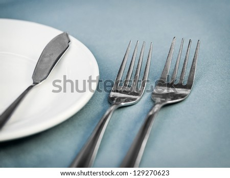 Served restaurant dinner table with two forks, white plate and knife on blue tablecloth