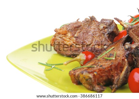 served savory plate: meat ribs with chives and red hot peppers on green