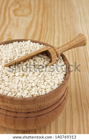Sesame seeds in wooden bowl close up