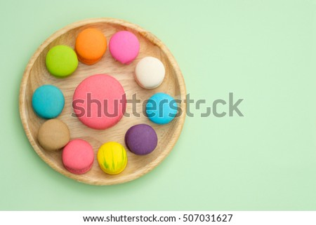 Set of different colorful macaroons Placed in a wooden tray on green background, Sweet and tasty for cooking and restaurant menu, Dessert beautiful, Top view, Space to write at right.