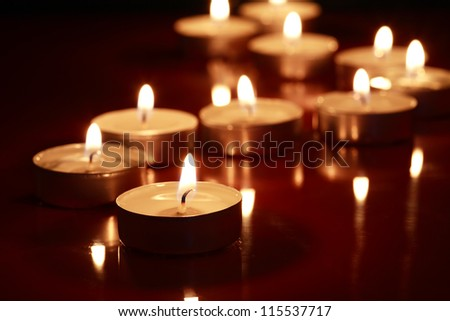 Set of lighting candles in a row on dark background