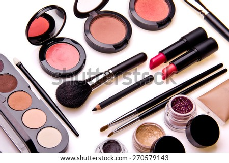 Set of professional cosmetic: make-up brushes, shadows, lipstick, nail polishes - partly isolated with shadows on white background. Overhead view. Front part.