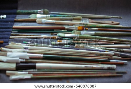 Set of various brushes of artist  on a dark background. Abstract composition