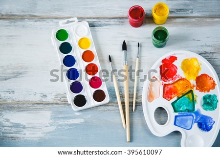 Set of watercolor paints, brushes for painting on old vintage wooden background top view