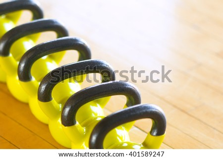 Set of yellow dumbbells with black handles lying on the parquet floor in a row