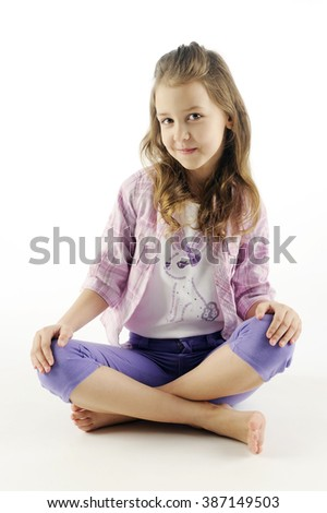 Seven-year girl cute smiling sitting with legs crossed, isolated on white