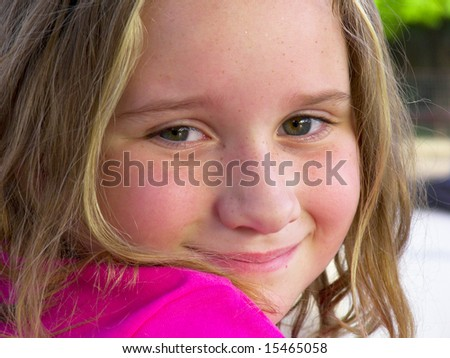 Seven year old girl smiling wearing a pink shirt