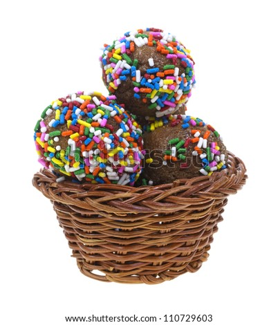 Several fresh donut holes sprinkled with colorful jimmies in a small basket on a white background.