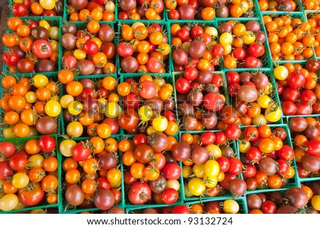 Several green plastic baskets filled with cherry tomatoes