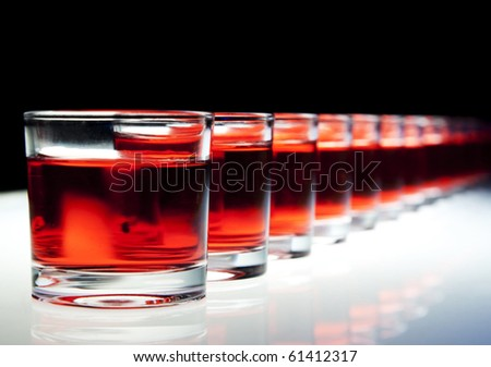 Several red alcohol shots on a bar.