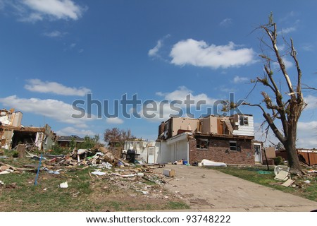 Severe tornado damage is very apparent in the light of a beautiful blue sky sunny day.
