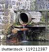 Sewage pipe on a dam - stock photo