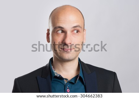 Sexy bald man looking away over gray background