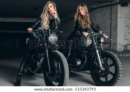 Sexy biker girls sitting on vintage custom motorcycles. Beautiful women with Healthy Long Hair ringlets wearing stylish leather jackets