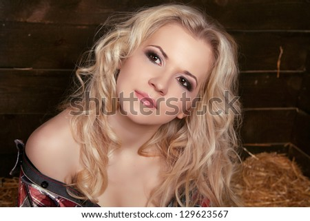 Sexy blond woman with curly hair on natural background