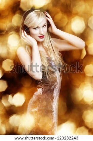 Sexy blond woman with headphones on golden background
