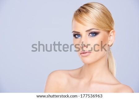 Sexy blue-eyed blond woman wearing dark eye makeup looking at the camera close up head portrait