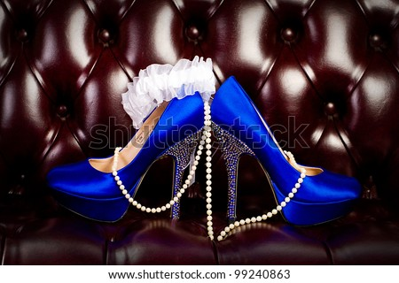 sexy blue high heel shoes with a pearl necklace dangling over the top