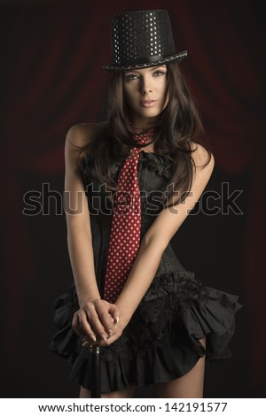 sexy brunette woman in cabaret show wearing dark corset, hat and red tie. Posing with stick on black background