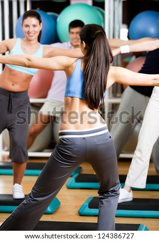 Sexy coach exercises with her group at the gym in a body shaping class