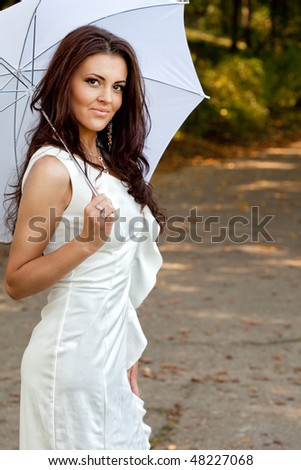 Sexy elegant young woman with umbrella outdoor