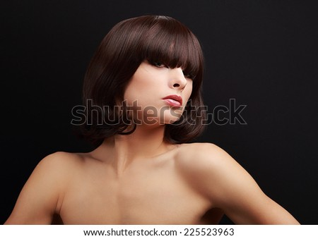 Sexy female model with short hairstyle posing on black background