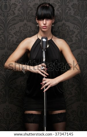 Sexy female singer wearing black dress holding a retro microphone over Damask wallpaper