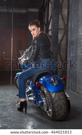 Sexy girl on a motorbike in a studio