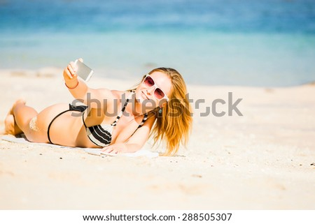 Sexy happy blond young woman in sunglasses taking selfie on the beach enjoying summer holidays, leying on white sand. Holidays, vacation, lifestyle concept