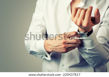 Sexy man buttons cuff-link on French cuffs sleeves luxury white shirt. Tonal correction